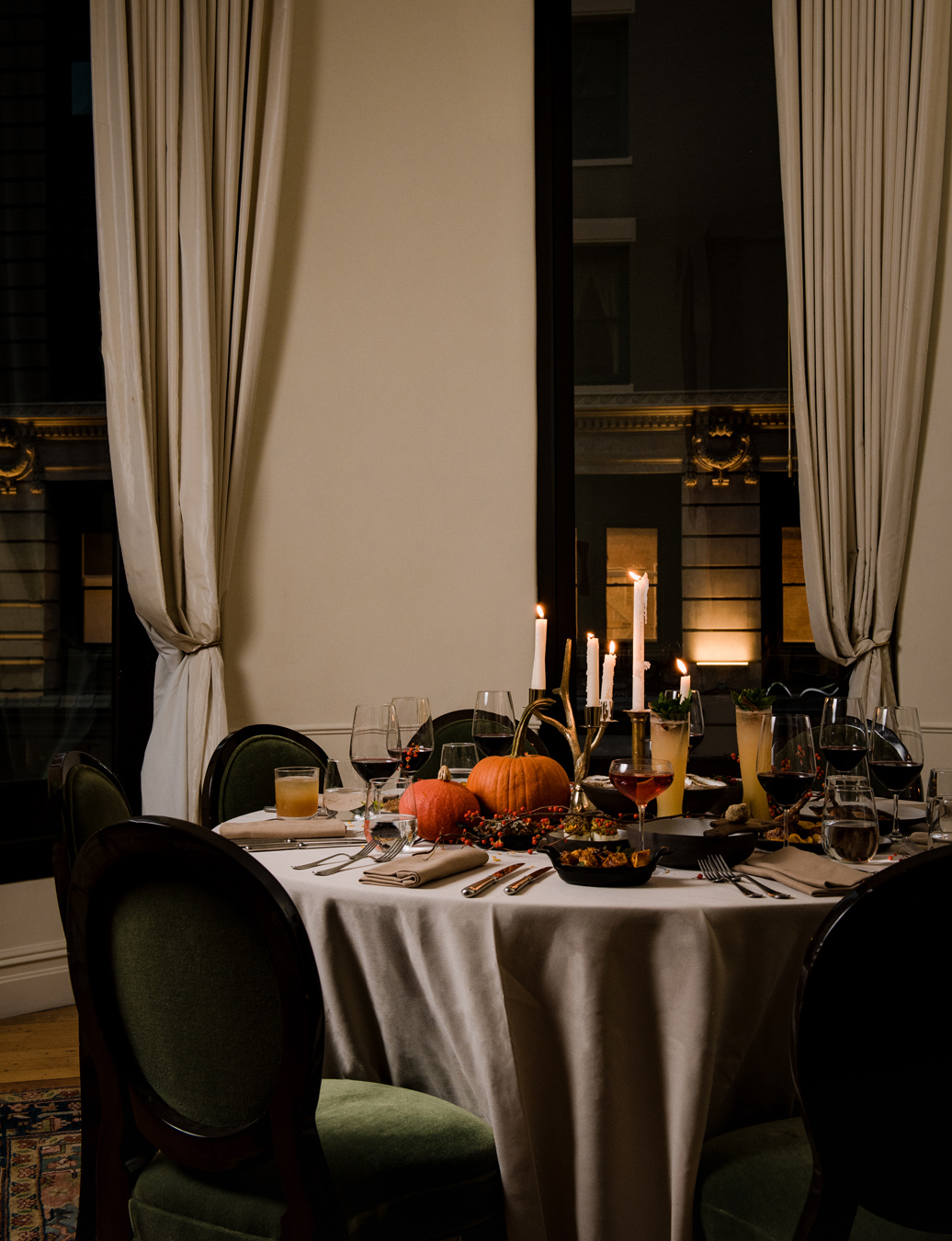 Thanksgiving candle light dining table with decorative pumpkins