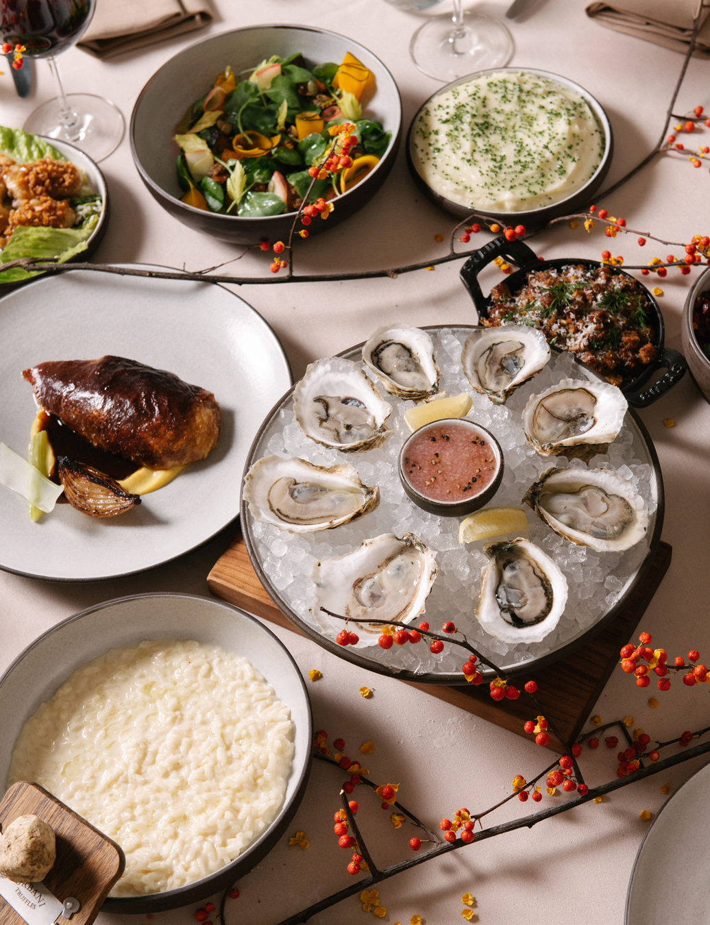 Overhead view of plate of oysters on ice, chicken entree, and other appetizers
