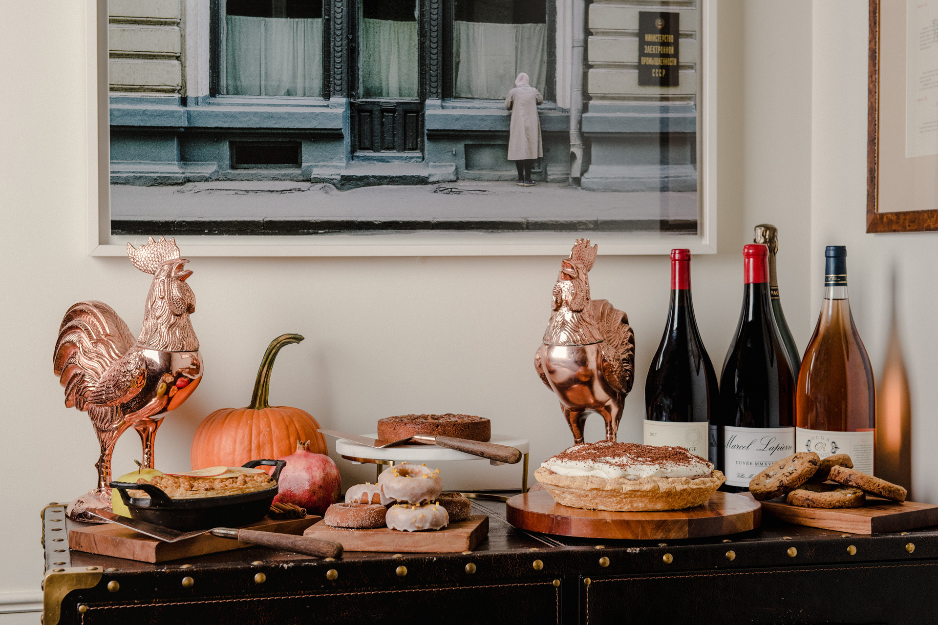 Table with desserts, wine bottles, and metal statues of roosters