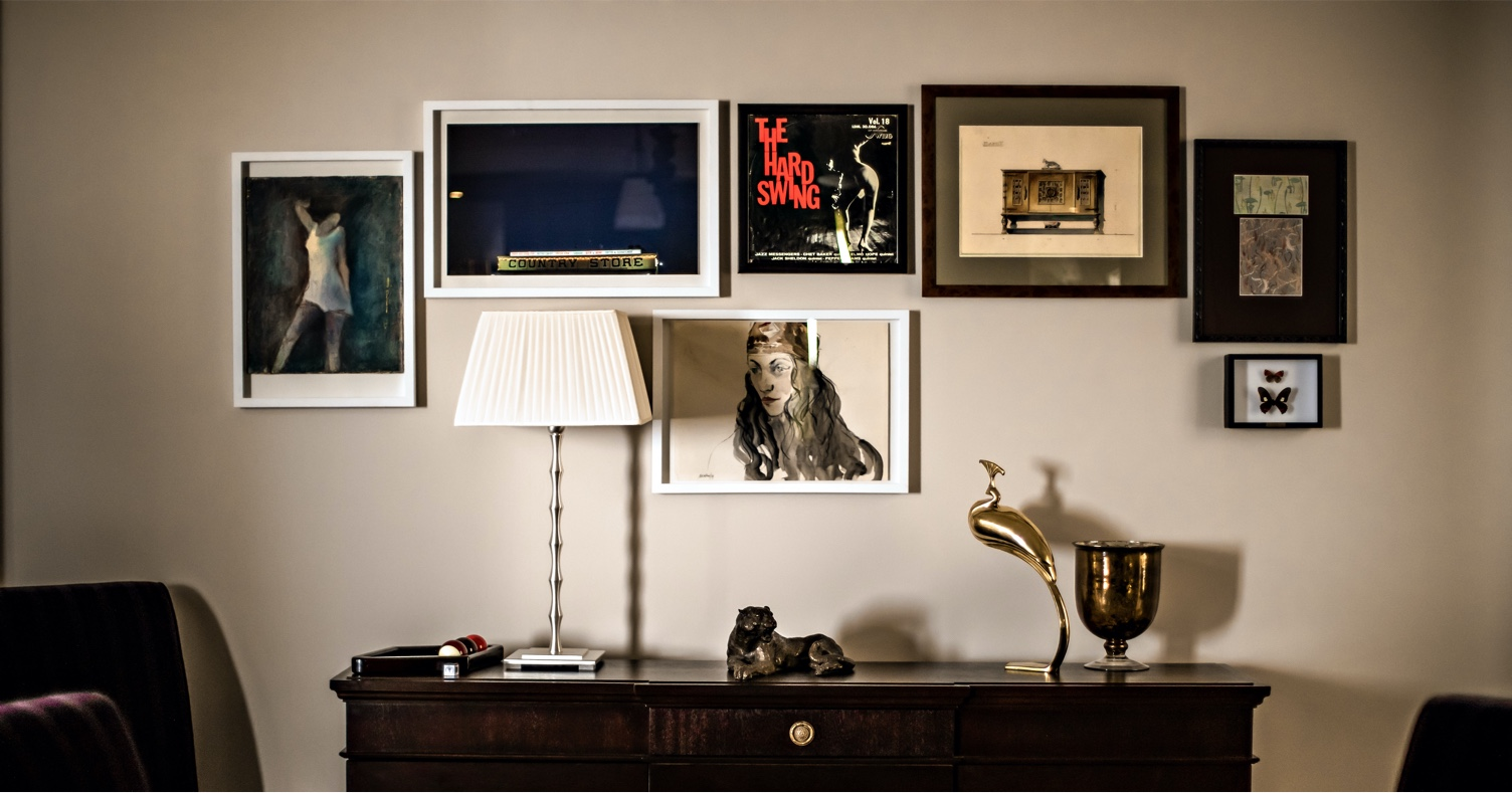 Room with drawer, lamp, metal sculptures ad wall with assorted contemporary framed art.