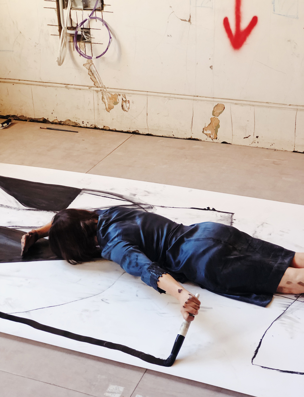 Woman stretched on the floor, lying on canvas, painting a line with a broad brush