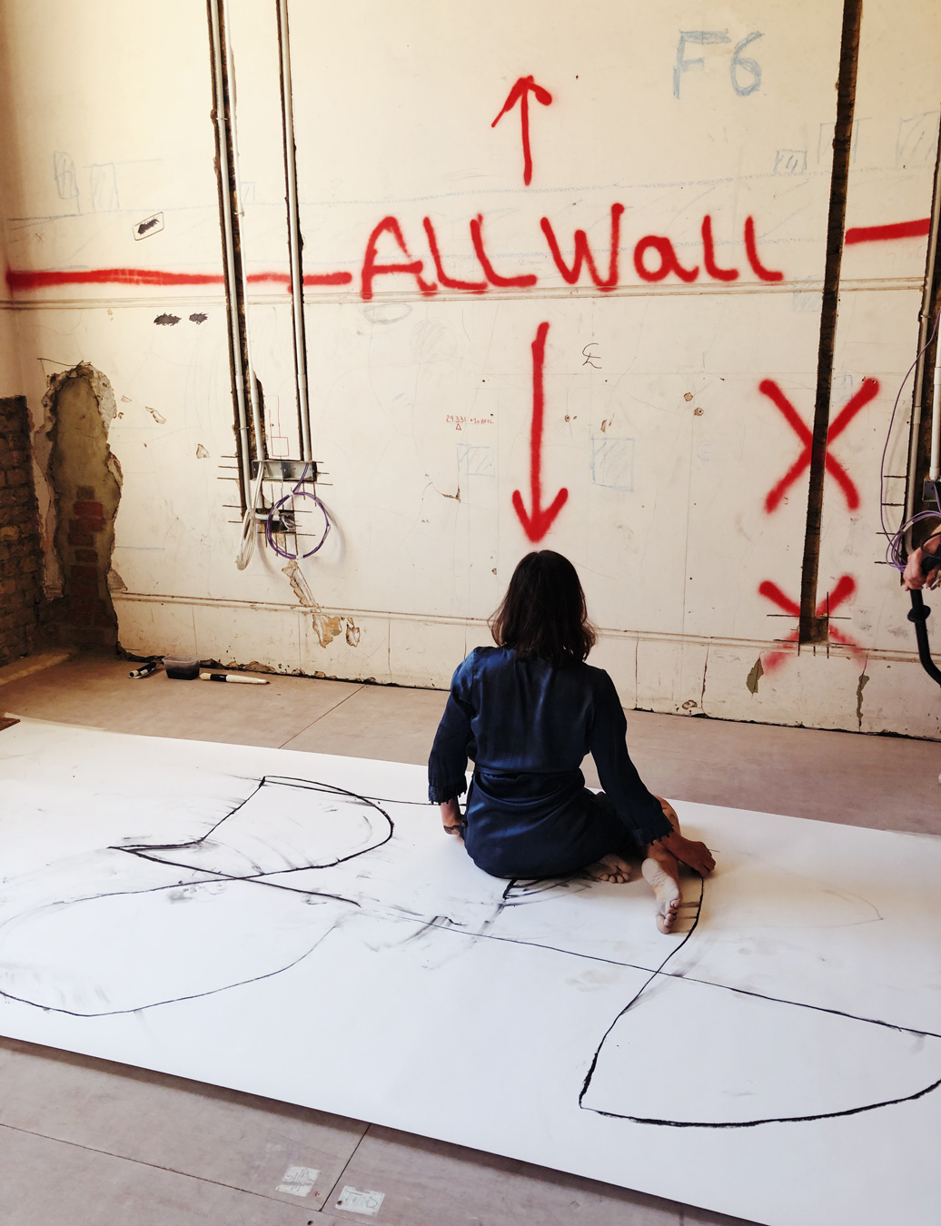 Woman sitting barefoot on canvas, facing wall with pray painted sign that says