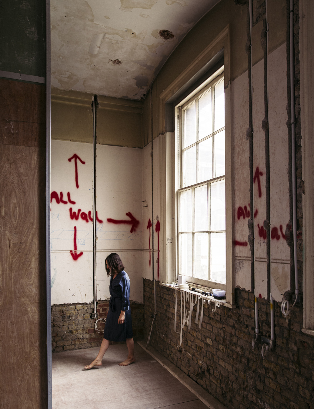 Woman walking barefoot inside room with partially exposed brick walls and spray-painted arrows