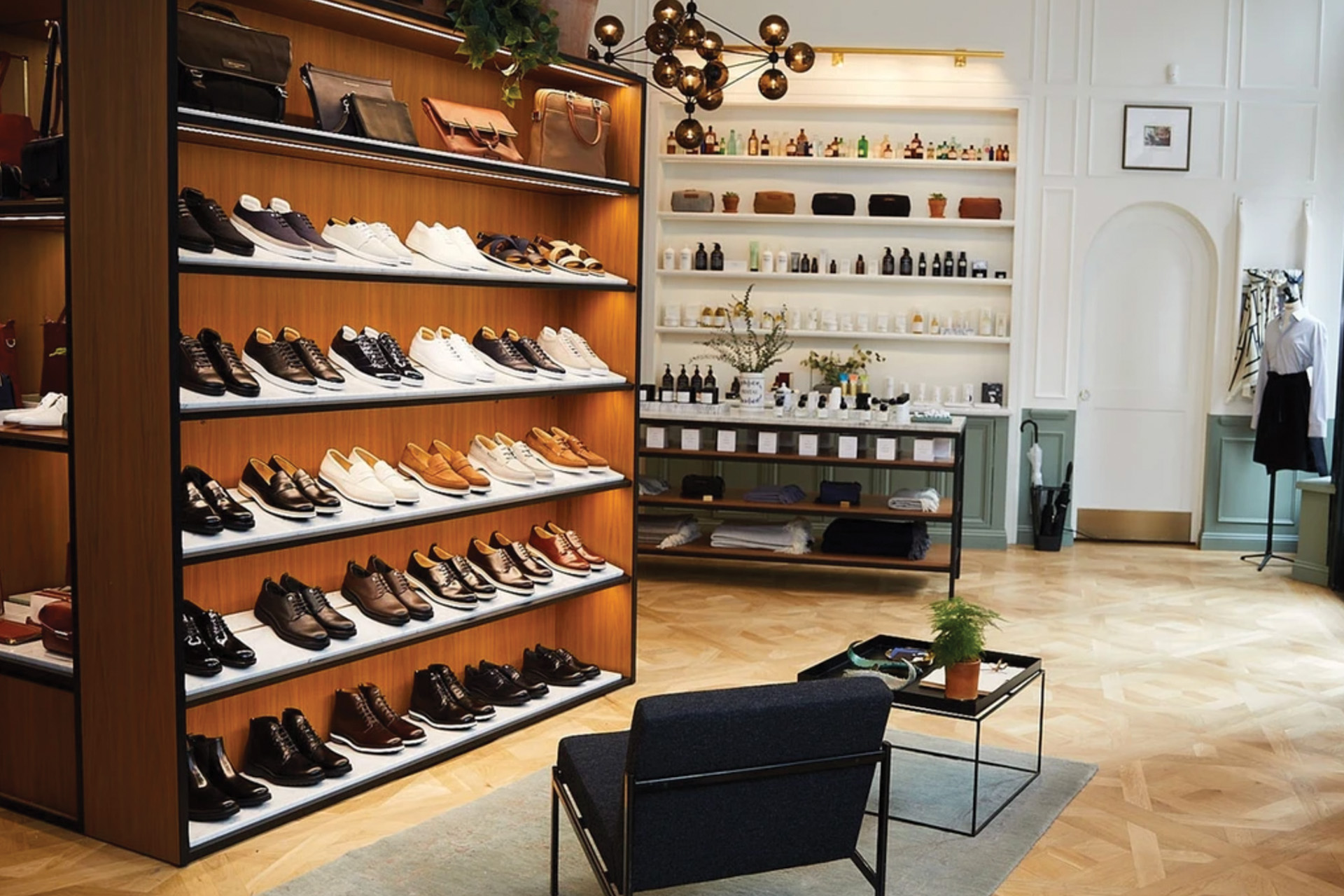 Retail store with shoes and leather goods display and table and wall with various skin care products.